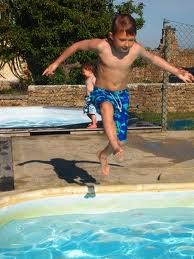 kid jumping into a pool